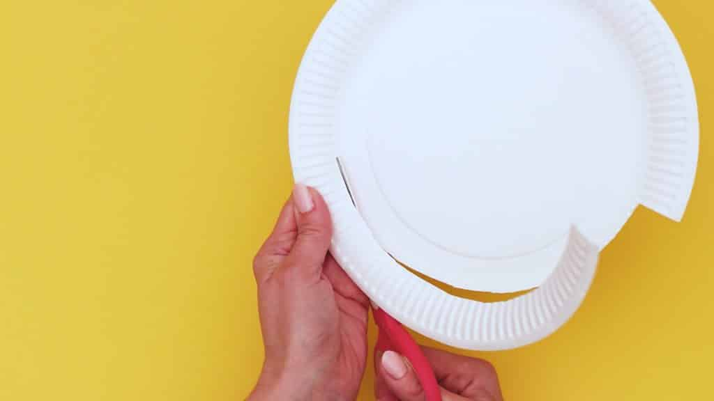 Image showing half of the rim of a paper plate being cut off.