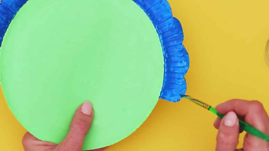 Image showing the paper plate being painted green and blue.