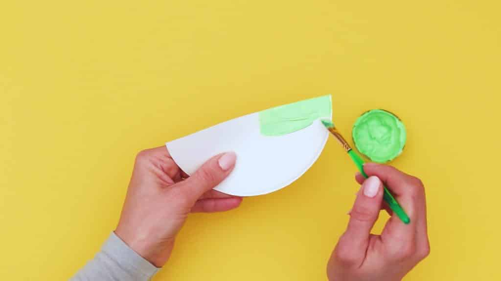Image showing a semi-circle cut out from a paper plate being painted green.
