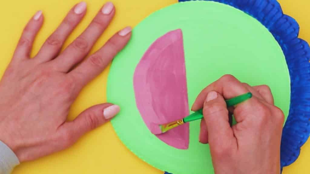 Image showing a pink semi circle being painted onto the main paper plate.