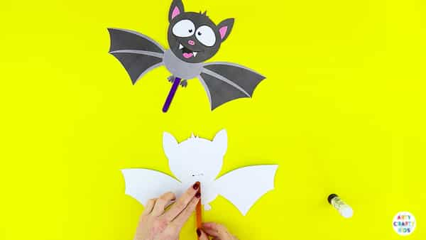 Halloween Crafts for Kids | Complete the paper bat toy with a stick to flap the wings.