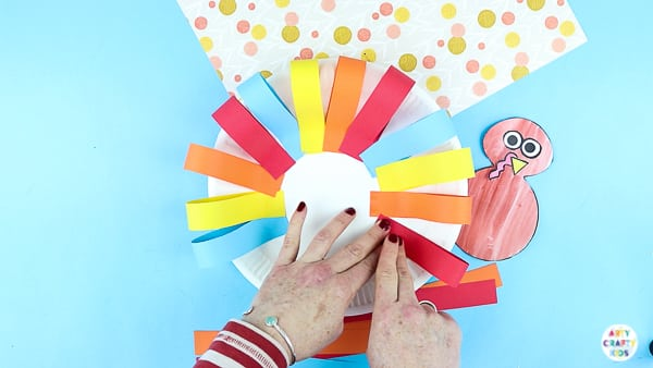 Arty Crafty Kids | Creating a paper plate turkey craft with strips of paper.
