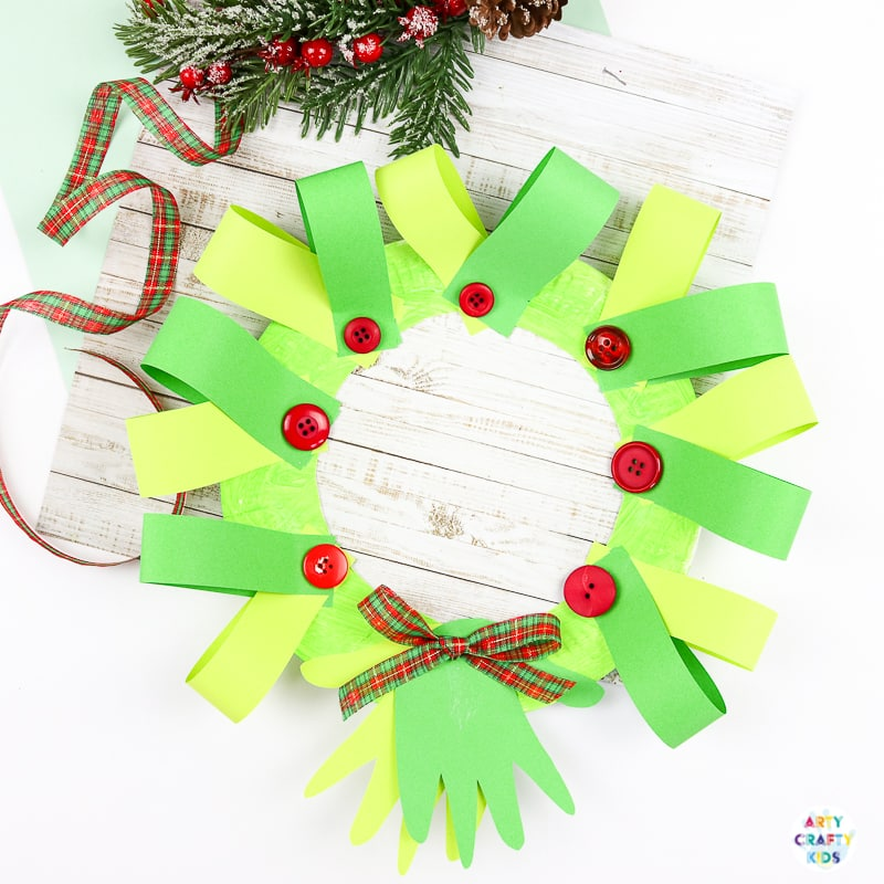Easy Paper Plate Handprint Christmas Wreath Craft for kids. A n easy Christmas craft that kids will love to make either at home or within the classroom. With added handprints, this craft also doubles up as a special keepsake craft for the festive season.