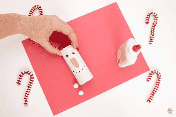 Add ear muffs to the paper roll snowman.
