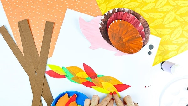 Cut out a handful of leaf shapes from tissue paper, using colorful Autumn color shades.