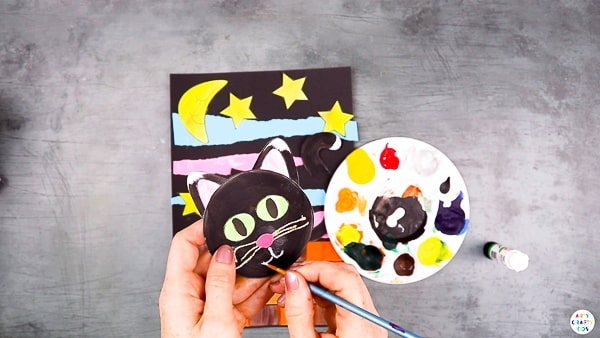 Add detail to the black cats face with whiskers, eyes and a cute little nose.