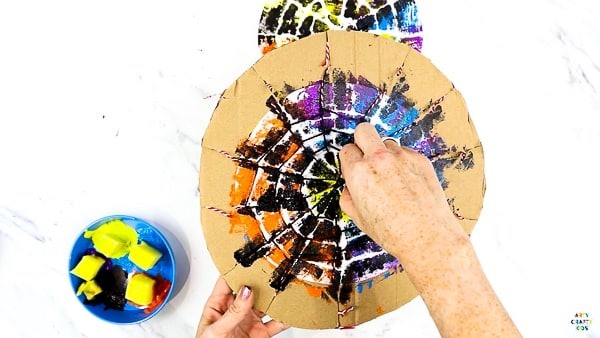 Cut the string and lift the paint parts from the centre to reveal the spider web.