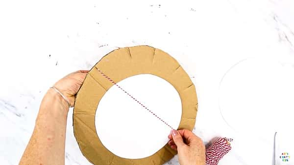 Add a circular piece of white cardstock and begin threading across in a clock formation.