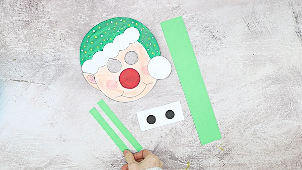 Once the elf template is colored in, cut out the elements and cut out a further three green strips; One strip should be wide and the full length of a piece of A4 card, the remaining two short and slim - log enough to cover the eye holes and support the long strip.
