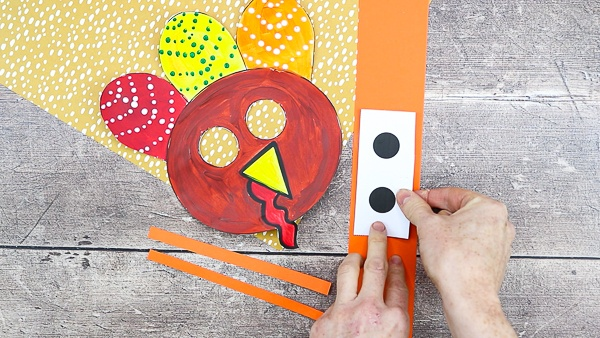 Cut out the turkey elements and cut out three strips of colored cardstock; one long piece and two short (approx 3-4 inches).