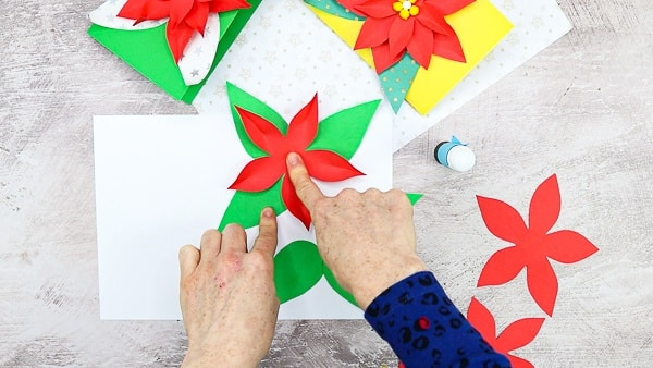 Once the poinsettia petals have been pinched, glue for the first and largest layer on top of the leaves.