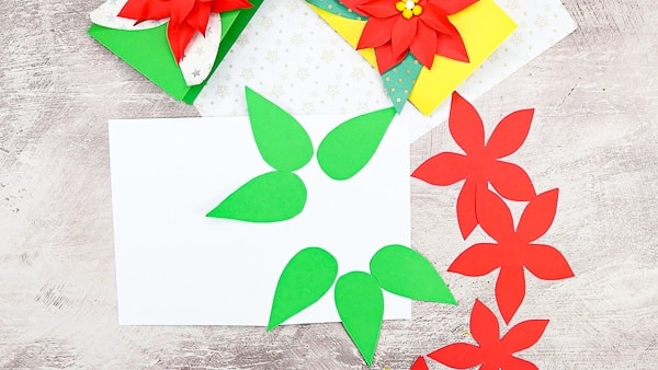 Secure the green leaves to the a piece of white cardstock to start building the Christmas card.