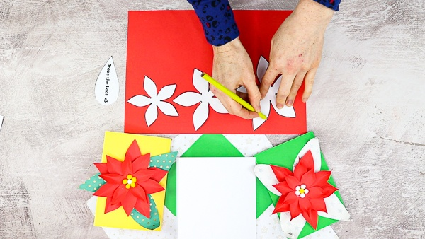 Trace the elements of the poinsettia flower onto red and green paper.
