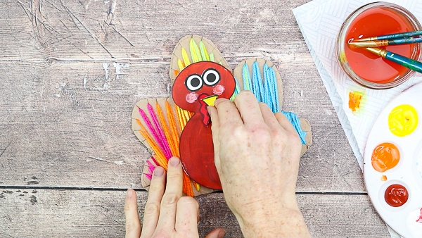 Add facial features to the turkey to complete the yarn wrapped Turkey craft.