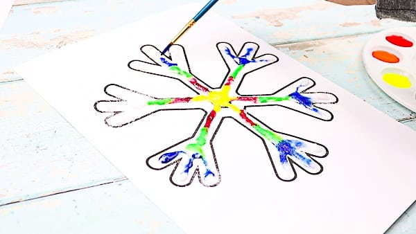 Continue painting the snowflake to transform it into a rainbow snowflake.