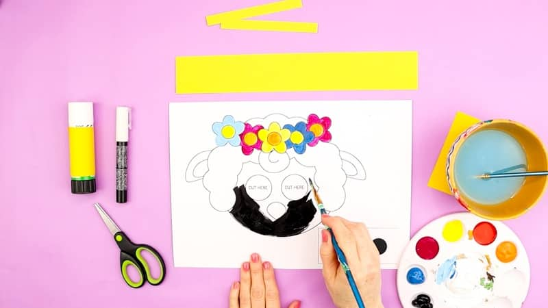 Coloring in the moving eyes lamb template with black paint and colors for the flowers.