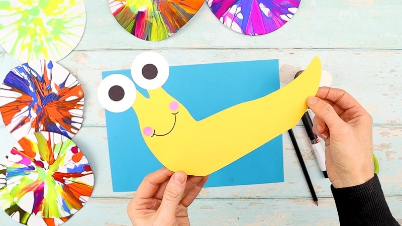 Assemble the snail: adding eyes, a smile and cute little cheeks.