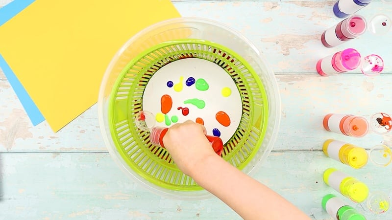 Add paint to the white card stock within the salad spinner. Use lots of different colors.