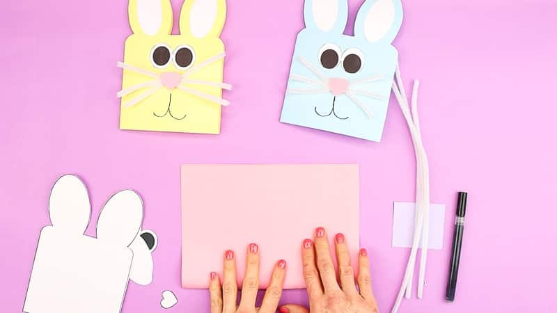 Image showing cut out Easter Bunny Card elements and hands folding a sheet of cardstock.
