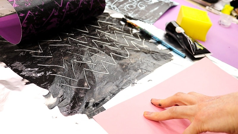 Image showing a piece of purple card stock being peeled gently away from a zig-zag print on the aluminium foil. A mono print can be revealed.