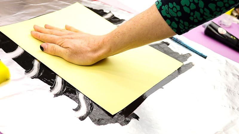 Image showing a piece of card being placed down onto the print.