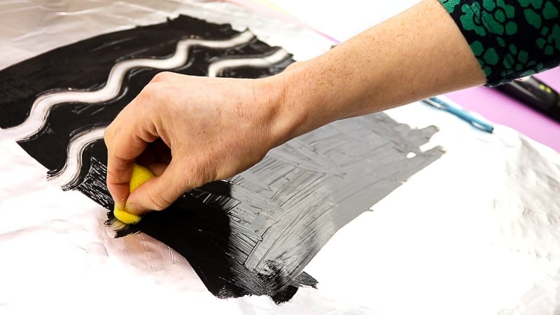 Image showing a pattern being drawn into black paint on aluminium foil with a sponge - the first print of the mono print process.