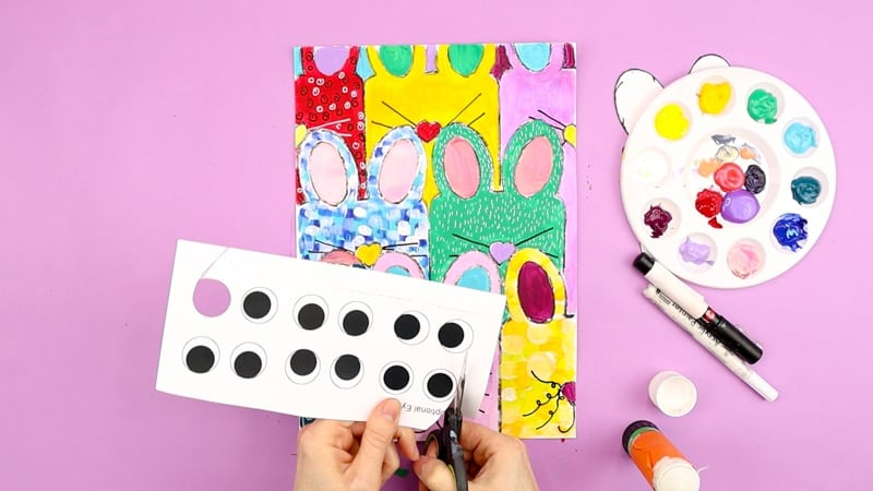 Image showing a collection of eyes being cut from the template and affixed to each bunny.