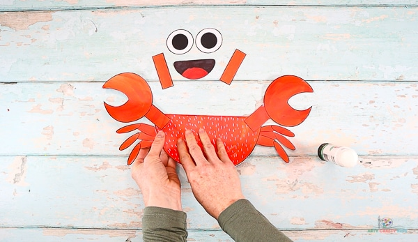 Affix both sets of crab legs to either side of the crabs body.