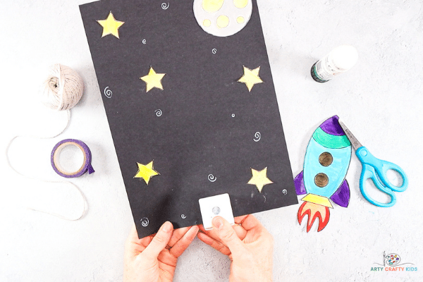 Create a space background on black cardstock.