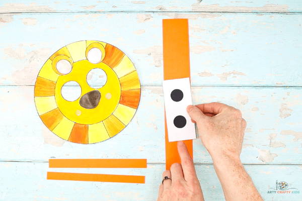 Image showing the eyes being glued to the middle of a long and wide strip of orange cardstock.