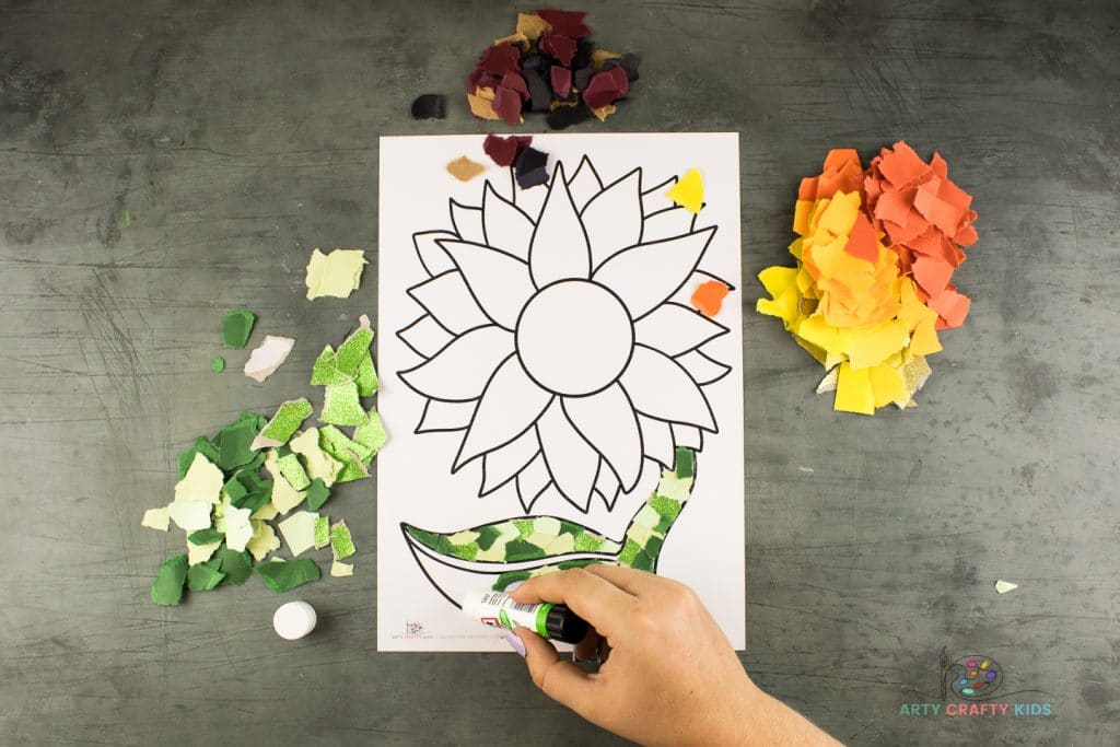 Image showing glue being applied to the leaf of the sunflower template.