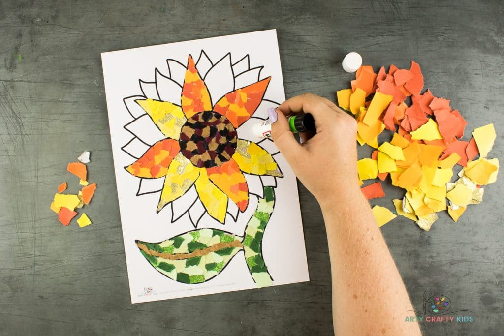 Image showing glue being applied to one of the petals of the sunflower, surrounded by bright yellow and orange colored paper pieces.