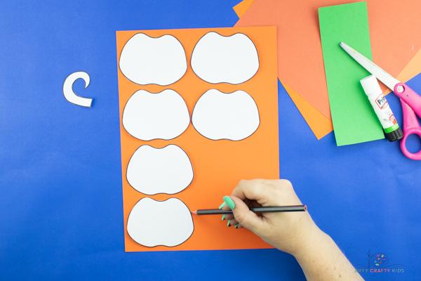 Image montrant 6 éléments d'artisanat de citrouille en papier découpés à partir du modèle et tracés sur du papier cartonné orange.