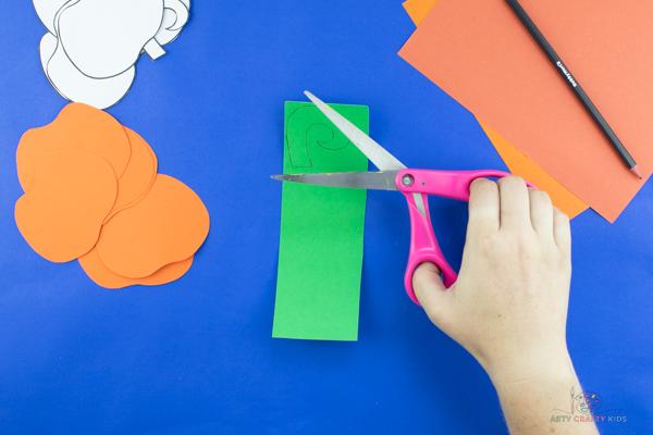 L'image montre une citrouille orange découpée et une cigogne verte tracée sur du papier.