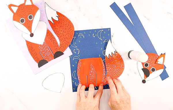 Imagine showing a hands gluing the fox's body and tail being stuck to the bottom of the backing cardstock.