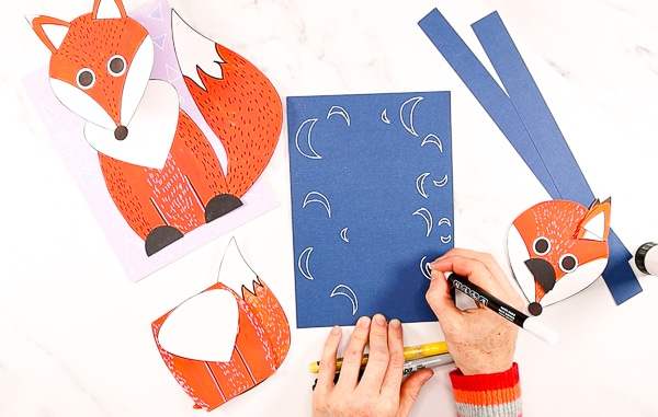 Hand showing moons being doodled onto a piece of a5 backing card.