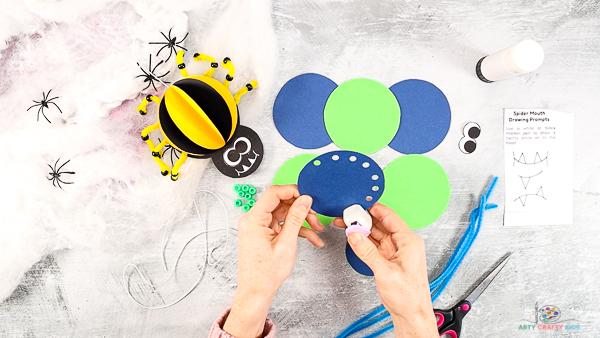 Image montrant une main utilisant une perforatrice pour créer 9 trous dans l'une des pièces circulaires.