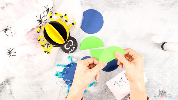 Image montrant des mains pliant les morceaux circulaires verts et bleus restants de papier cartonné en deux.